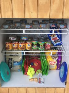 The pet pantry is filled with food, treats and toys for pets.