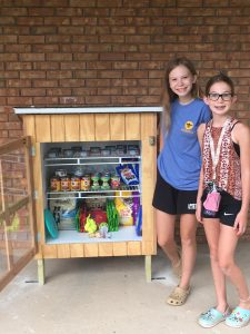 Emma Wiker and her sister, Ellen, stand beside the pet pantry they opened in Athens, Ill.