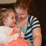 A mom holds her young daughter with complex medical needs and smiles at her