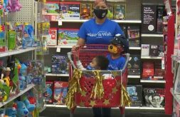 Shyterria Jordan pushes a decorated shopping cart with her son T'Aubrae and his big brother inside during a shopping spree