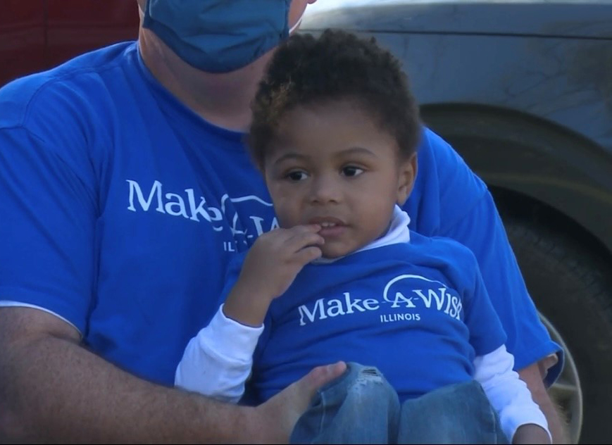 3-year-old T'Aubrae smiles as he watches a special community parade in his honor