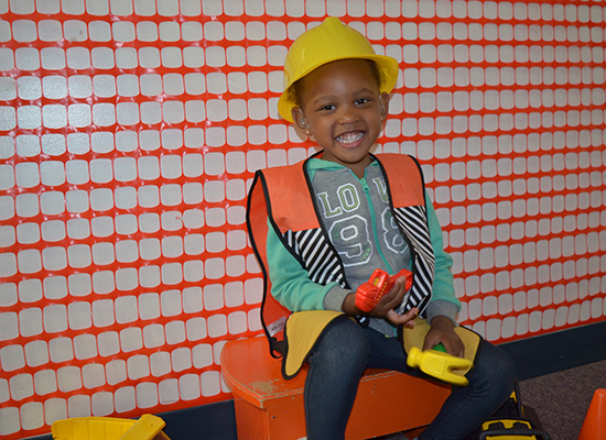 A young girl with hearing aids smiles while dressed up as a construction worker