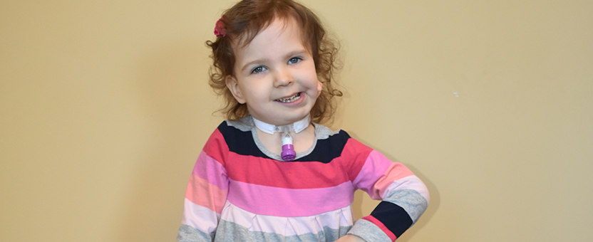 A little girl with a tracheostomy and craniofacial difference smiles
