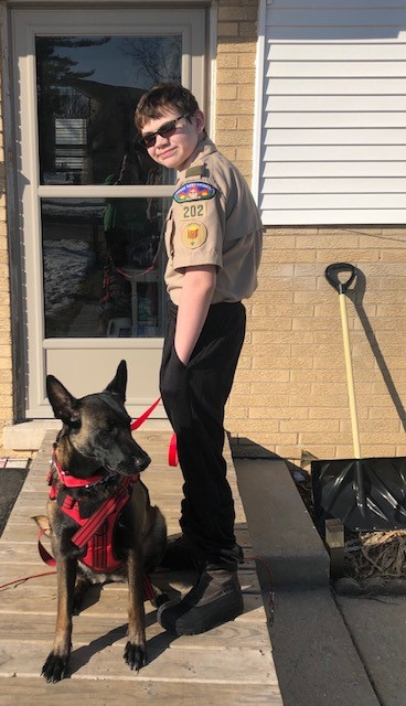 Nathan Lichucki in his Scout uniform with his service dog, Dakota