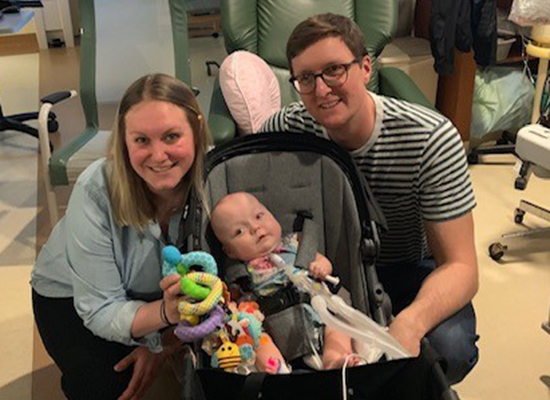The Wolff family smiles and poses together in a hospital room