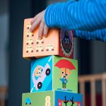 close-up of a child's hands stacking large blocks